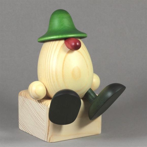 Eierkopf Anton auf Kante sitzend, grün