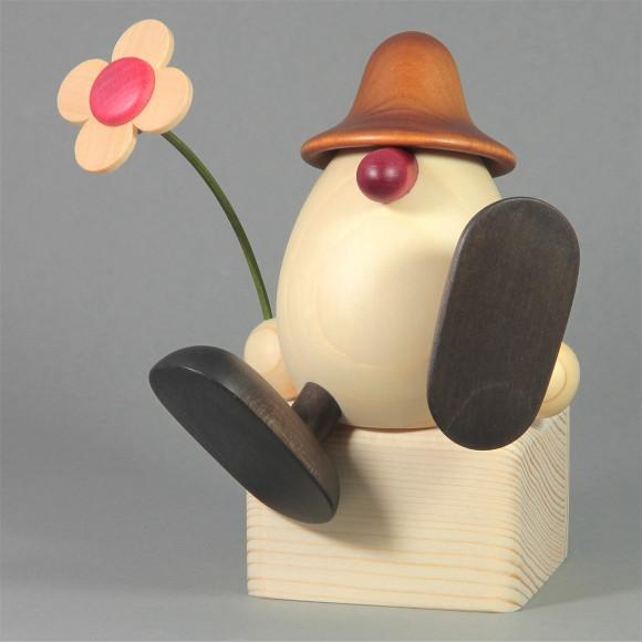 Eierkopf Alfons mit Blume auf Kante sitzend, braun