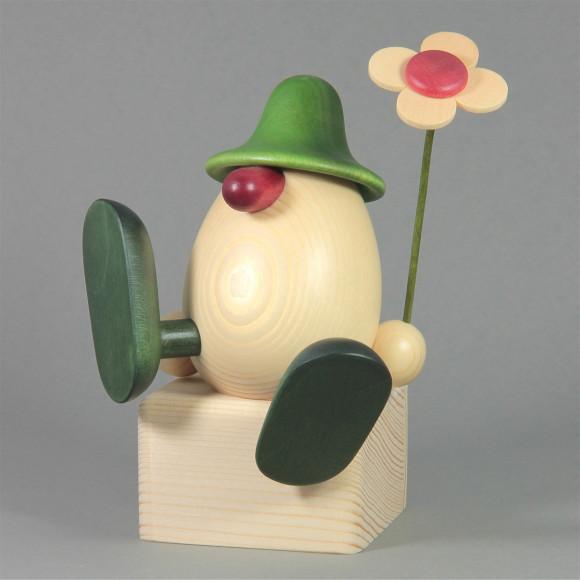 Eierkopf Alfons mit Blume auf Kante sitzend, grün