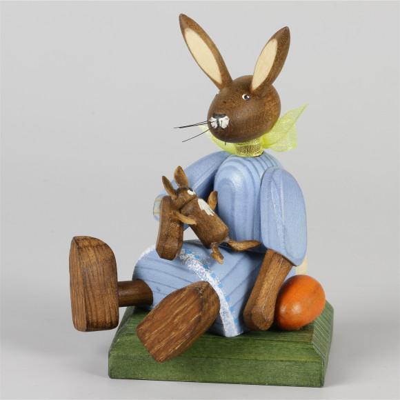 Kleines Hasenmädchen mit Puppe, sitzend, blau