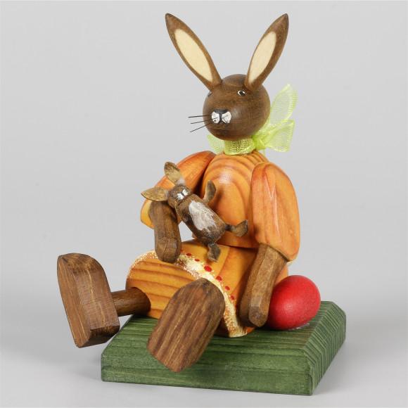 Kleines Hasenmädchen mit Puppe, sitzend, orange