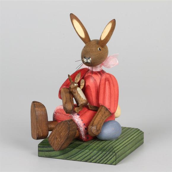 Kleines Hasenmädchen mit Puppe, sitzend, rot
