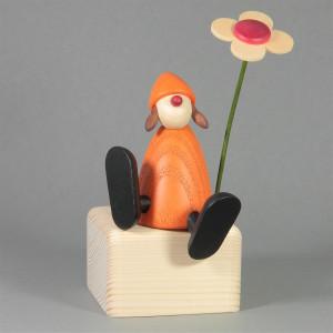 Gratulantin Sophie mit Blume auf Kante sitzend, gelb