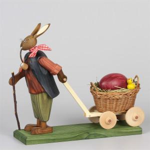 Osterhasengroßvater mit großem Ei im Handwagen