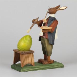 Osterhasengroßvater mit großem Ei beim Bemalen