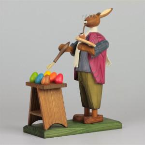 Osterhasengroßvater mit kleinen Eiern beim Bemalen