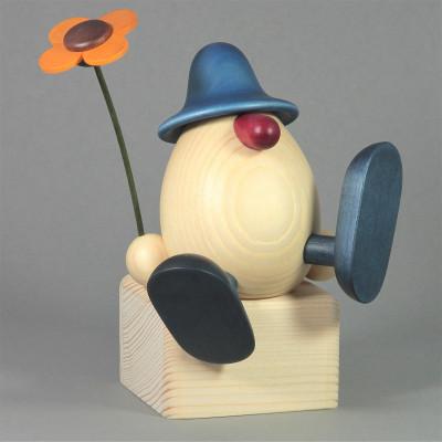 Eierkopf Alfons mit Blume auf Kante sitzend, blau