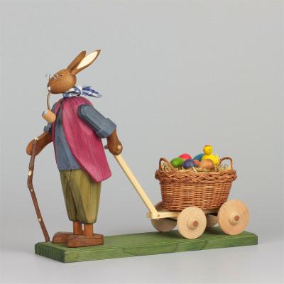 Osterhasengroßvater mit kleinen Eiern im Handwagen
