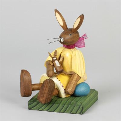 Kleines Hasenmädchen mit Puppe, sitzend, gelb
