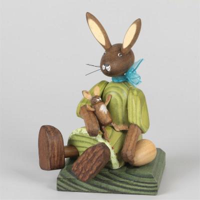 Kleines Hasenmädchen mit Puppe, sitzend, grün