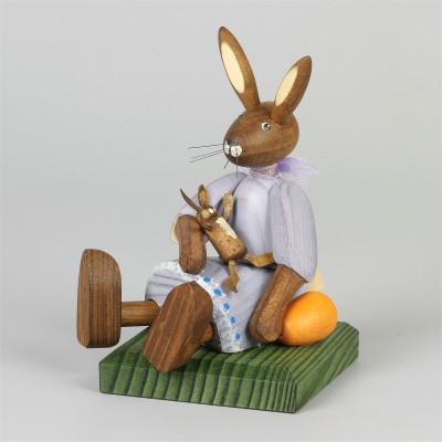 Kleines Hasenmädchen mit Puppe, sitzend, lila